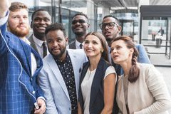 Self portrait of stylish successful, professional team, afro-american black man with stubble shooting selfie with hand royalty free stock photo