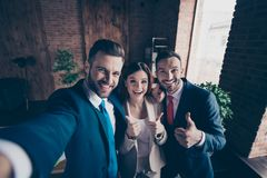 Self-portrait of three nice stylish beautiful handsome cheerful optimistic hr managers bankers economists showing. Thumbup great in loft industrial interior royalty free stock images