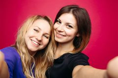 Two positivity girls taking self portrait smiling, posing at pink background. Self portrait of two beautiful, positivity girls, taking photo,smiling and posing royalty free stock photography