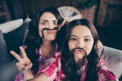 Self-portrait of two nice cute sweet attractive lovely pretty cheerful cheery positive wavy-haired girls sisters sitting. On divan showing v-sign fake mustache royalty free stock photography