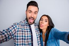 Self portrait of young, comic, cheerful, caucasian, attractive,. Beautiful, lovely, cute, positive, couple in shirts, showing tong out to the front camera of Stock Photos