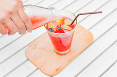 Self pouring ice tea serve with ice cube with fruits frozen insi. De in a garden Royalty Free Stock Images