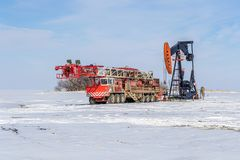 Self-propelled drilling rig and pump jack in winter time on the. Self-propelled red color drilling rig and pump jack in winter time on the field with white snow Stock Photos