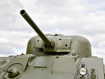 Self-propelled gun. Long rifled barrel. Against the bright sky.  green. Military action. Four lights on the armor. The armored vehicle Stock Photography