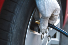 Self Pumping car tires. Pumping car tires in the service station. People at work. The man inflates car tires royalty free stock images