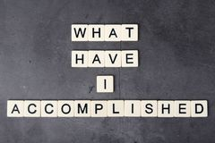 What have I accomplished motivational phrase formed with tile letters. Self-question to inspire and motivate stock photo