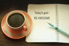 Todays goal - be awesome. Self reminder. Self notes on a notepad arrangement with coffee and a pen. Natural wooden dark table royalty free stock image