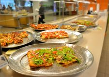 Self serve pizza at a cafeteria with diners and waiter Royalty Free Stock Photos