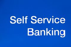 Self service banking sign on blue background. Finance business concept stock image