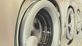 Self service washing machine working. Close up of industrial self service washing machine working stock footage