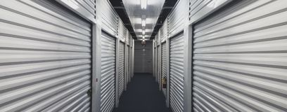 Self storage unit doors on each side of an indoor hallway. Indoor storage units. Hallway lined with metal garage doors on each. Creates a 3D perspective stock image