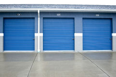 Self storage units. Three blue garage doors of self storage units Royalty Free Stock Photo