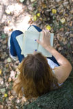 Self-study. Women reading interesting book alone in a forest Stock Photos