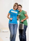Self-sufficient friends painting with paint roller Royalty Free Stock Images