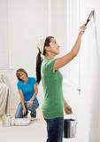Self-sufficient woman painting with paint brush Royalty Free Stock Photography