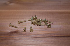 Self-tapping screws on a wooden background Royalty Free Stock Photos