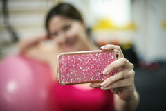 Self time. Portrait of girl taking self picture in an old gym. Focus is on hand Royalty Free Stock Image