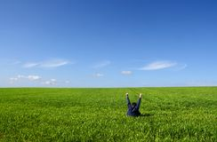 Self victory. A man sitting alone in a green field, with arms up Stock Photo