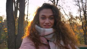 Self-video of smiling caucasian curly-haired woman in sunshine talking in videochat in autumnal park. Self-video of smiling caucasian curly-haired woman in stock video