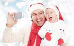 Selfe w zimie szczęśliwy rodzinny tata bawić się z córką i fotografujący na telefonie komórkowym Fotografia Stock