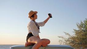 Selfi-Foto des netten Mädchens auf Dach der alten Maschine auf Ufermeer, Selfphoto der jungen Frau zum Retro- Auto stock footage