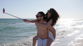 Selfi photo couple on vacation, Friends have fun in travel, cheerful girl jumping on guy`s back, Mobile phone on selfie. Stick removes funny photos of young stock video