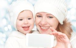 Selfie在冬天 有女儿和被拍摄的自已的愉快的家庭母亲在手机 免版税库存照片