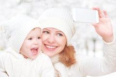 Selfie在冬天 有女儿和photogr的愉快的家庭母亲 免版税库存图片