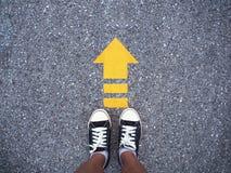 Selfie运动鞋在混凝土路的黑色鞋子有黄色箭头锂的 库存照片