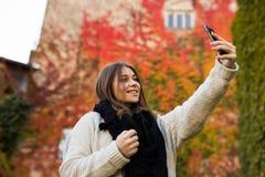 Selfie взятия девушки на желтой и красном цвете выходит предпосылка Стоковое Изображение RF