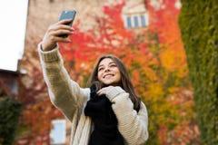 Selfie взятия девушки на желтой и красном цвете выходит предпосылка Стоковая Фотография