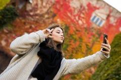 Selfie взятия девушки на желтой и красном цвете выходит предпосылка Стоковое Изображение