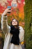 Selfie взятия девушки на желтой и красном цвете выходит предпосылка Стоковое фото RF