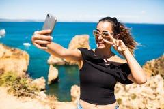 Selfie взятия женщины красоты латинское от телефона на верхней части красивой скалы s и утесах Атлантического океана в Португалии Стоковые Изображения RF