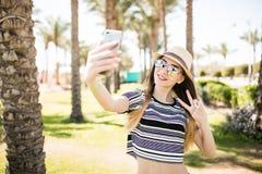 Selfie взятия женщины на телефоне и победа подписывают на предпосылках ладоней Концепция призвания лета Стоковая Фотография RF