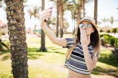 Selfie взятия женщины на телефоне на ладонях и посылает предпосылки поцелуев Концепция призвания лета Стоковые Изображения RF