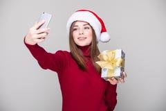 Selfie взятия женщины на телефоне с шляпой рождества Стоковое фото RF