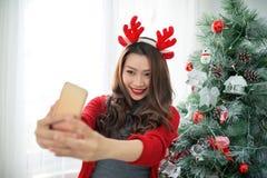 Selfie взятия женщины на телефоне с gif рождества владением шляпы рождества Стоковые Фото