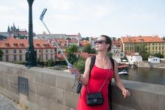 Selfie взятия женщины с мобильным телефоном в Праге, чехии Женщина с smartphone на ручке на мосте над рекой Турист w девушки Стоковая Фотография
