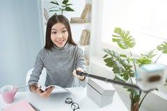 Selfie девушки сидя на таблице и держа журнал в ее руках Девушка смотрит к камере и усмехаться Стоковые Изображения RF