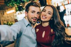 Selfie 2 красивых людей сидя совместно в баре Он фотографирует они пока она как раз усмехается с Стоковое Фото