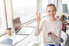 Selfie усмехаясь девушки сидя на таблице Она показывает символ части к камере Девушка любит ее работа и Стоковые Фотографии RF