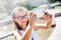 Selfie 戴括号和眼镜的美丽的逗人喜爱的女孩笑为selfie的 免版税图库摄影