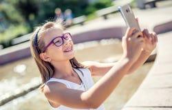 Selfie 戴括号和眼镜的美丽的逗人喜爱的女孩笑为selfie的 免版税库存图片
