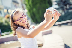 Selfie 戴括号和眼镜的美丽的逗人喜爱的女孩笑为selfie的 库存照片