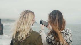 Πίσω άποψη δύο νέων γυναικών που παίρνουν selfie τις φωτογραφίες στην ακτή της θάλασσας κοντά στους troll βράχους toe στην Ισλανδ απόθεμα βίντεο