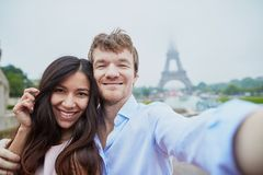 采取selfie的愉快的夫妇在埃佛尔铁塔附近 库存照片