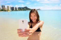 采取乐趣在威基基海滩的女孩智能手机selfie 库存照片