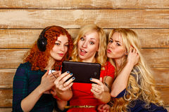 姐妹在耳机做乐趣selfie,听到音乐 免版税图库摄影