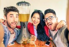 采取与滑稽的舌头和啤酒塔的愉快的朋友selfie 库存照片